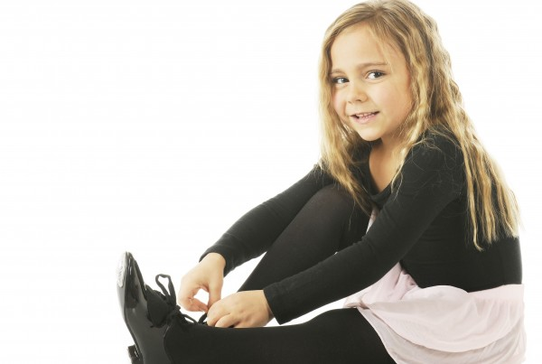 A beautiful kindergarten girl tying on her tap shoes.  On a white background.